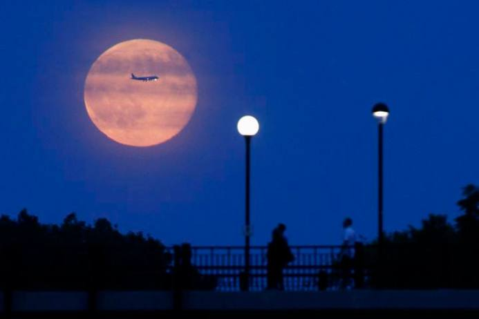 Aircraft passes in front of a Supermoon rising over the Rideau Canal in Ottawa